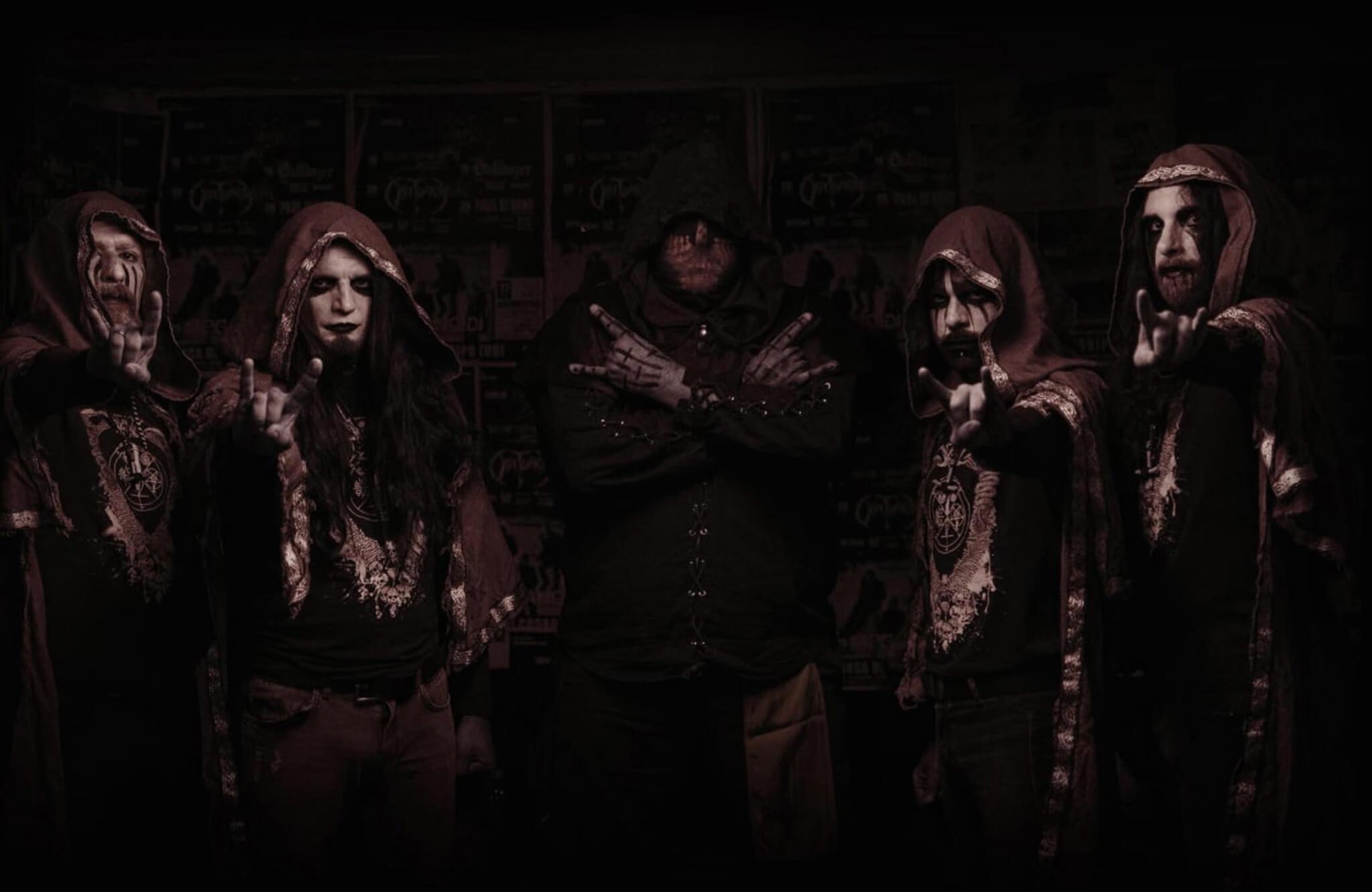 Dark image, 5 hooded figures pose with heavy metal makeup